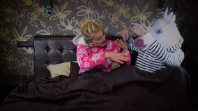 La coppia insolita si siede sul letto in camera da letto alla moda che gesticola e che balla stock footage