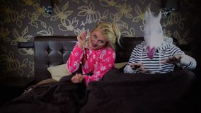 La coppia insolita si siede sul letto in camera da letto alla moda che gesticola e che balla video d archivio
