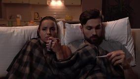 La coppia malata si siede insieme Sono coperti di coperta Bevande della ragazza dalla tazza Il tipo ottiene il termometro e lo es