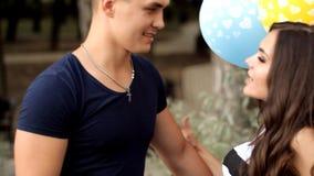 La coppia nell'amore con i palloni passa insieme il tempo in un parco di festa stock footage