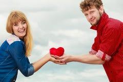 La coppia nell'amore giudica il cuore rosso all'aperto Immagini Stock