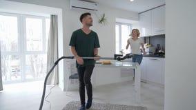 La coppia nell'amore sta divertendosi in cucina, uomo felice sta ballando con l'aspirapolvere con la ragazza cui canta con una si