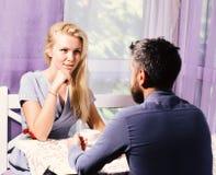 La coppia nell'amore tiene le tazze di caffè alla tavola La donna ed il fronte civettuolo e l'uomo hanno un affare immagine stock
