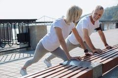 La coppia ottimistica che fa l'allungamento si esercita insieme Fotografia Stock Libera da Diritti