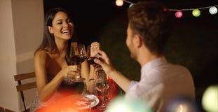 La coppia ride mentre alzano i loro vetri di vino Immagine Stock