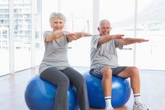La coppia senior che fa l'allungamento si esercita sulle palle di forma fisica Fotografie Stock Libere da Diritti