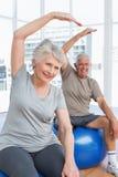 La coppia senior che fa l'allungamento si esercita sulle palle di forma fisica Fotografia Stock
