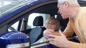 La coppia senior posa con l'automobile alla gestione commerciale video d archivio