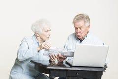 La coppia senior sta esaminando le fatture responsabili Fotografia Stock