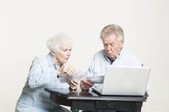 La coppia senior sta esaminando le fatture responsabili Fotografie Stock Libere da Diritti