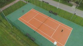 La coppia senior sta giocando a tennis sulla corte in parco verde Vista superiore verticale aerea video d archivio