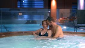 La coppia si rilassa in una vasca calda all'aperto Giovane donna felice ed uomo che si rilassano in acqua calda vicino allo stagn video d archivio