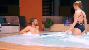 La coppia si rilassa in una vasca calda all'aperto Giovane donna felice ed uomo che si rilassano in acqua calda vicino allo stagn archivi video