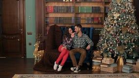 La coppia si siede su un piccolo sofà vicino all'albero di Natale stock footage