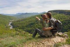 La coppia si siede sul bordo e guarda alle montagne, punti della ragazza Immagini Stock Libere da Diritti