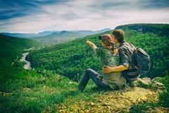 La coppia si siede sul bordo e guarda alle montagne, punti della ragazza, l'effetto di retro macchina fotografica Immagine Stock
