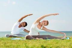 La coppia sorridente che fa l'yoga si esercita all'aperto Immagini Stock Libere da Diritti