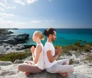 La coppia sorridente che fa l'yoga si esercita all'aperto Fotografie Stock Libere da Diritti