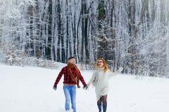 La coppia sorridente di amore sta divertendosi mentre correva lungo la foresta nevosa Immagini Stock