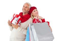 La coppia sorridente nella tenuta di modo dell'inverno presenta e sacchetti della spesa Fotografie Stock