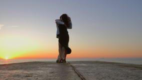 La coppia spagnola energetica contro lo sfondo dell'alba e dell'oceano dimostra gli elementi del ballo latino sensuale stock footage