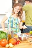 La coppia sportiva felice sta preparando l'alimento sano sulla cucina leggera fotografia stock