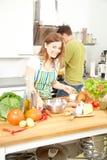 La coppia sportiva felice sta preparando l'alimento sano sulla cucina leggera fotografia stock libera da diritti