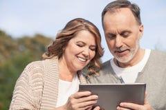 La coppia sposata anziana allegra sta guardando una compressa Fotografia Stock