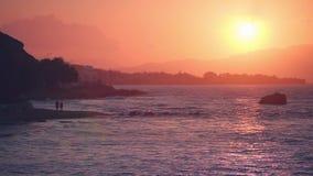 La coppia sta camminando nel tramonto sopra il mare archivi video