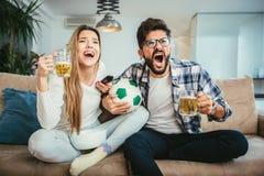 La coppia sta guardando il calcio sul sofà Fotografia Stock Libera da Diritti