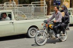 La coppia sta guidando una motocicletta sulla strada affollata, Kashan, Iran Fotografia Stock