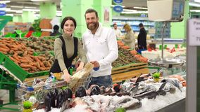 La coppia sta scegliendo i frutti di mare congelati per la cena nel supermercato video d archivio