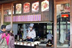 La coppia sta scegliendo i pasti in un ristorante di portare via nella città Wuzhen, Cina dell'acqua Immagini Stock Libere da Diritti
