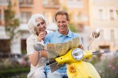 La coppia sul motorino sta sorridendo immagini stock