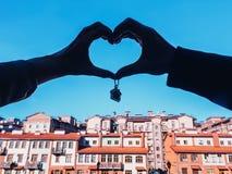La coppia tiene gli alloggi nuovi di chiavi la casa della tenuta della siluetta delle mani chiude a chiave il keychain a forma di Fotografie Stock