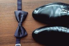 La corbata de lazo negra miente antes de los zapatos de cuero y de correa Novios que se casan mañana Imagen de archivo