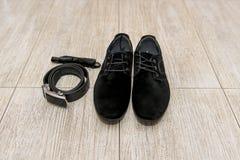 La corbata de lazo negra y los zapatos de cuero preparan la mentira al lado de la correa de pantalones Accesorios del novio, homb Fotos de archivo