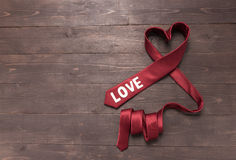 La corbata roja del corazón está en fondo de madera Fotografía de archivo