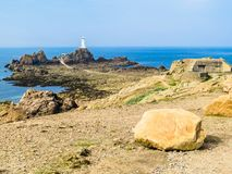 La Corbiere Lighthouse on the rocky coast of Jersey Island Stock Photo