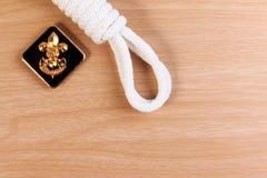 La corda bianca dell'esploratore di ordine con i boy scout d'annata badge sulla tavola di legno Immagini Stock Libere da Diritti