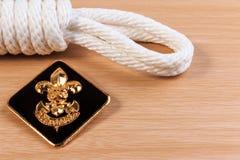 La corda bianca dell'esploratore di ordine con i boy scout d'annata badge sulla tavola di legno Fotografie Stock Libere da Diritti