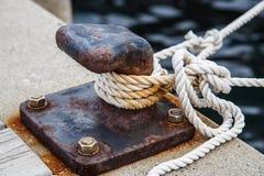 La corda per l'attracco della nave è aderita ad un pilastro fotografia stock