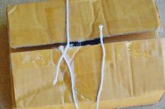 La corde de colis a coupé et ouvre la boîte brune de courrier Photos libres de droits