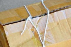 La corde de colis a coupé et ouvre la boîte postale brune Photos stock
