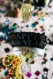 La corona de la Feliz Año Nuevo se sienta sobre el vidrio de Champán Foto de archivo