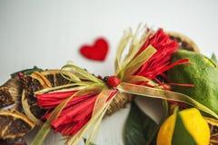 La corona di vimini con in forma di cuore, decorato con le foglie, limone, ha asciugato il limone Immagini Stock