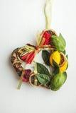 La corona di vimini con in forma di cuore, decorato con le foglie, limone, ha asciugato il limone Fotografia Stock