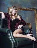 La corona que lleva de la mujer rubia joven en interior de lujo de hadas con la antigüedad vacía enmarca las piernas largas de la Imágenes de archivo libres de regalías