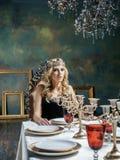 La corona que lleva de la mujer rubia joven en interior de lujo de hadas con la antigüedad vacía enmarca riqueza total Imagen de archivo libre de regalías