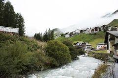 La corrente ed il ghiacciaio dalle alpi lo scorrimento della catena montuosa il più su ed il più esteso sono passato ai villaggi Immagini Stock
